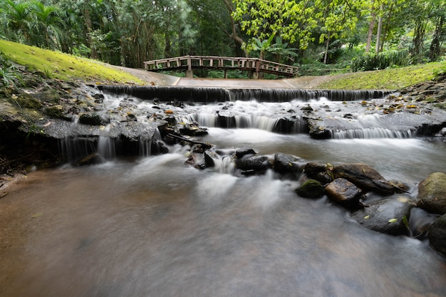 Small waterfall  with old wooden  bridge