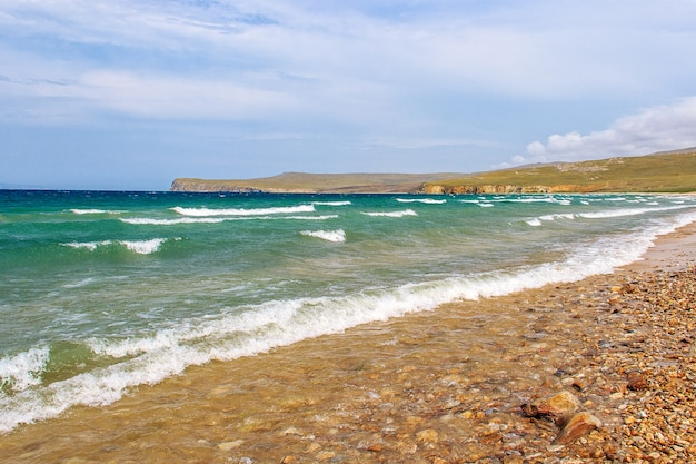 Небольшие волны несутся к галечному берегу озера байкал. остров ольхон, россия