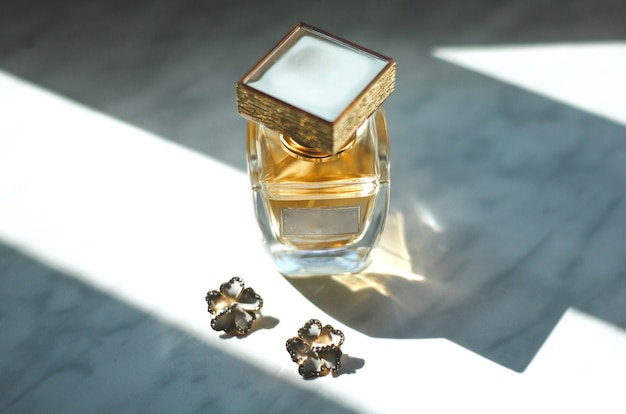 Small wedding flower earrings and stylish perfume scent bottle on the grey background in sun lights.