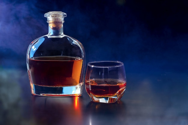 Small whiskey decanter with glass of spirits on a midnight blue background with copy space