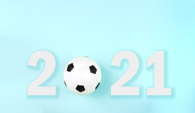 Small white black ball for football sport game on blue background with text 2021.