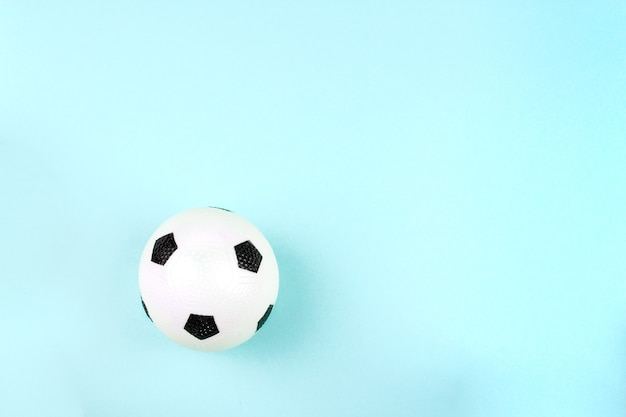 Small white black ball for football sport game on blue background.