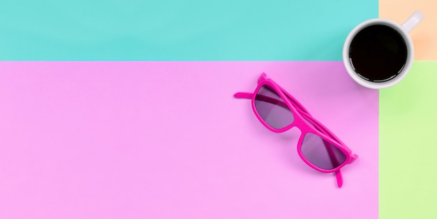 Small white coffee cup and pink sunglasses on background of fashion pastel pink, blue, coral and lime colors