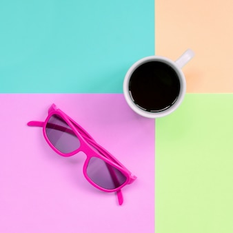 Small white coffee cup and pink sunglasses on fashion pastel pink, blue, coral and lime colors