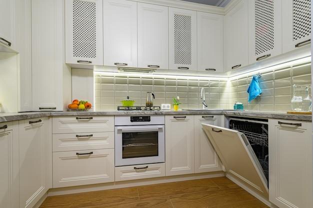小さな白い居心地の良い快適な現代的な古典的なキッチンのインテリア、食器洗い機のマシンのドアが開いています