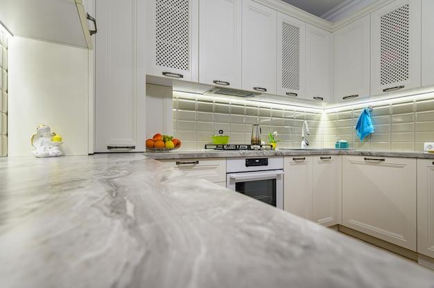 Небольшая белая уютная и удобная современная кухня в классическом стиле с деревянной мебелью, большим пространством