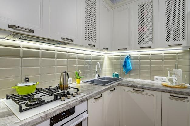 Маленькая белая уютная и удобная современная кухня в классическом стиле с деревянной мебелью