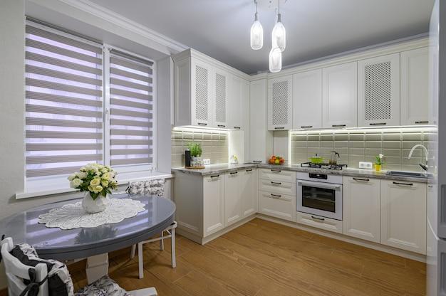 Небольшая белая уютная и удобная современная кухня в классическом стиле с деревянной мебелью