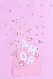 Маленькие белые цветы, светло-розовый конверт и слово amor на светло-розовом фоне, вид сверху