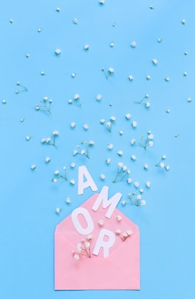Small white flowers, pink envelope and word amor on a light blue background top view