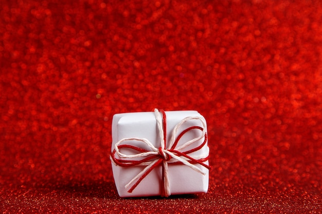 A small white gift on a red shiny, sequins in the side. the concept for valentine's day.