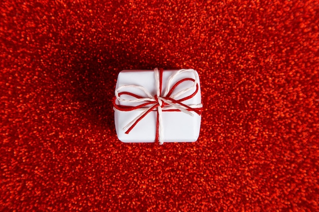 A small white gift on a red shiny, sequins in the side. the concept for valentine's day. Premium Photo
