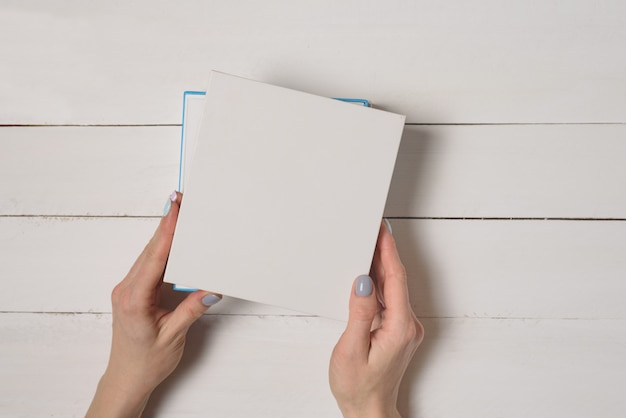 Small white half-open box in female hands. top view. white table