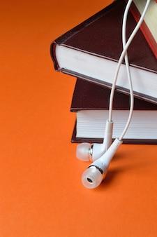 電話からの小さな白いヘッドフォンは、オレンジ色の背景の本のスタックの上にあります。