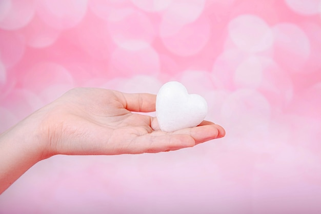 A small white heart in hand on pink background with bohe. greeting valentine's day card