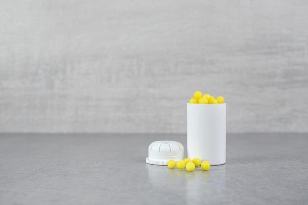 A small white jar of ascorbic acid pills on gray surface