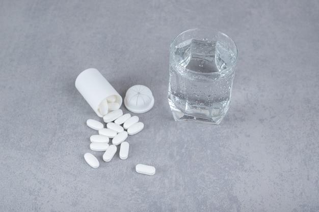 Un piccolo barattolo bianco di pillole bianche con un bicchiere di acqua pura su una superficie grigia
