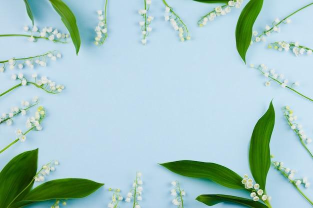Маленькие белые ландыши с большими зелеными листьями лежат на пастельно-синем фоне.