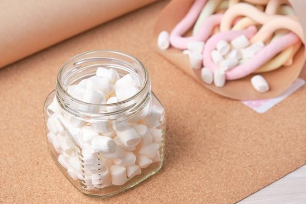 Маленькие белые зефиры для украшения и питья и украшения тортов в банке на фоне пробковой доски и мешочка с длинными зефирами спагетти, копировальное пространство