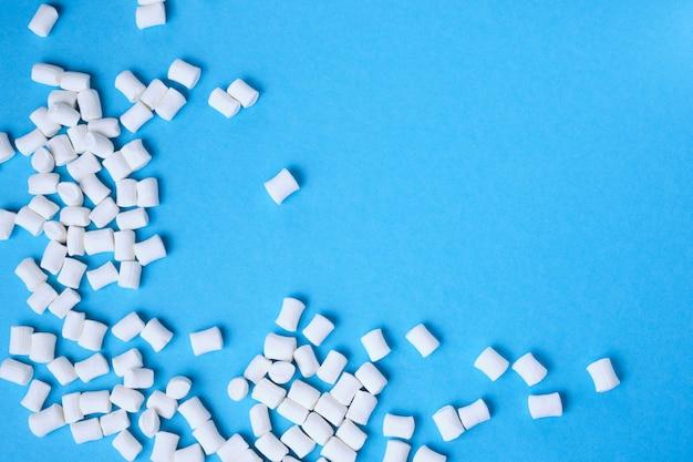 Маленькие белые зефиры разбросаны на синем фоне с копией пространства