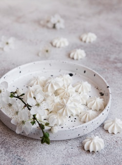 Small white meringues in the ceramic bowl on concrete background