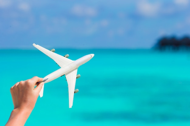 Small white miniature of an airplane on background of turquoise sea