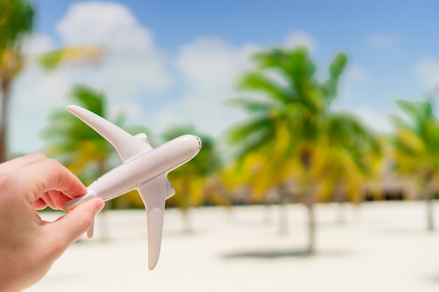 Small white miniature of an airplane on exotic beach and palmt rees