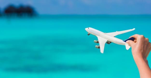 청록색 바다의 배경에 비행기의 작은 흰색 미니어처