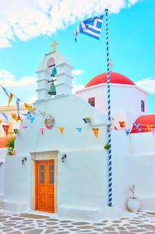 Small white orthodox church with greek flag in mykonos town, greece