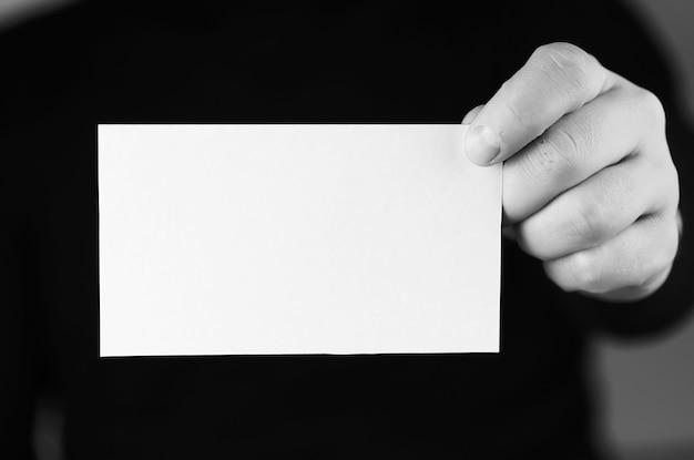 彼の手の男のモノクロの小さな白い紙
