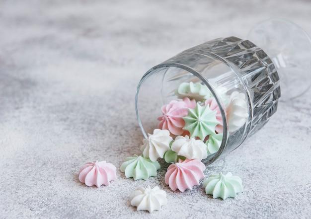 コンクリートの表面にグラスに入った小さな白ピンクと緑のメレンゲ
