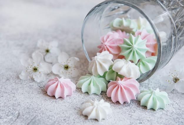 Маленькие белые розовые и зеленые безе в стакане на бетонной поверхности