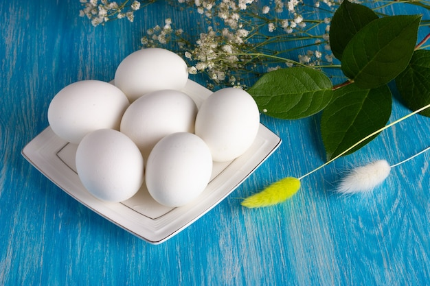 Small white plate with white eco eggs with flowers on the light-blue wooden