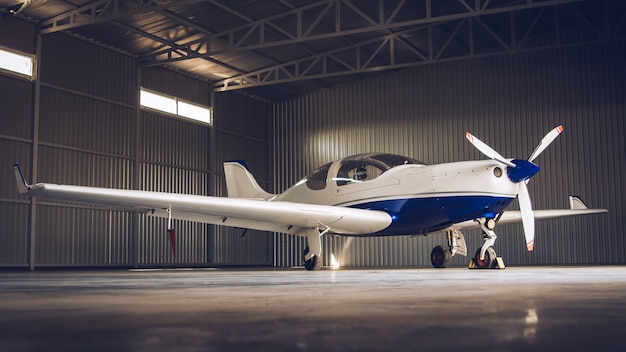 Small white private jet parked in the hangar