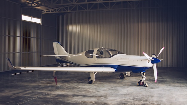 Маленький белый частный самолет припаркован в ангаре
