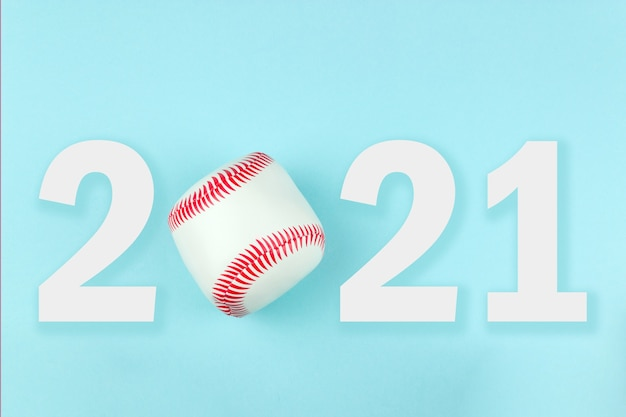 Small white red ball for baseball sport game on blue background with text 2021.