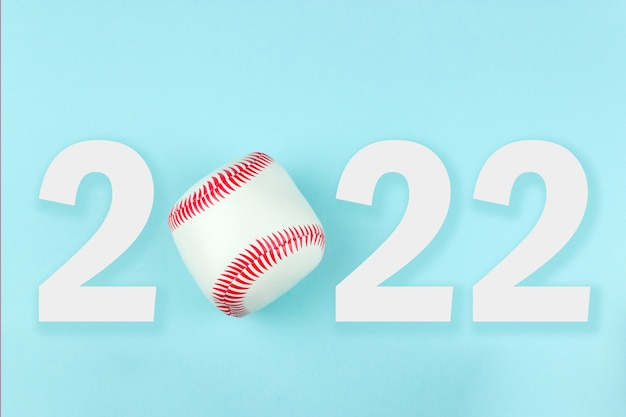 Small white red ball for baseball sport game on blue background with text 2022.