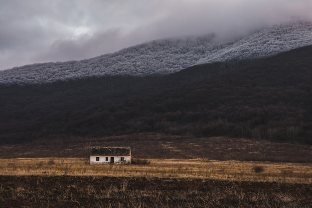 Small white single house in a field with fog on the mountain