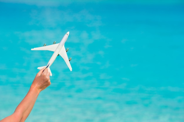 Small white toy airplane on of turquoise sea
