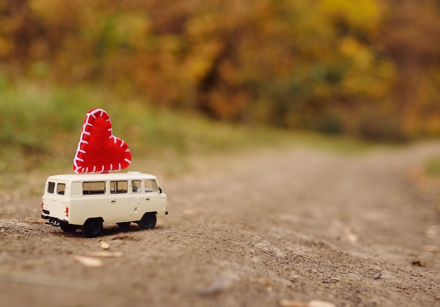 A small white toy car minivan is driven on the roof of a big red heart