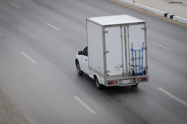 도로를 달리는 작은 흰색 트럭.