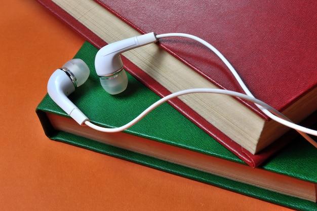 작은 흰색 유선 이어폰이 책 더미 위에 놓여 있습니다. 확대