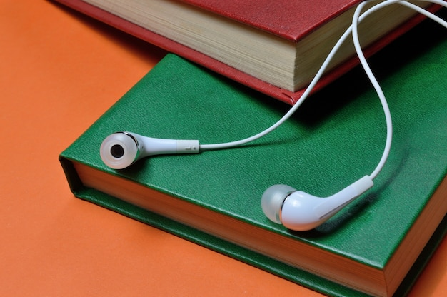 Маленькие белые наушники с проводом лежат на стопке книг. крупный план