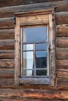 古い木造家屋の壁にある小さな窓古い歴史の家