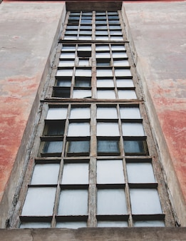 Small windows in an old high-rise building against the bright sky