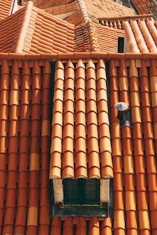 갈색 타일 지붕의 다락방 바닥에 있는 작은 창문