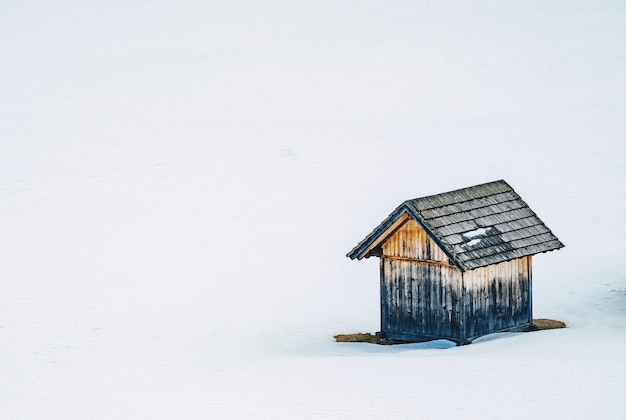 Small wooden barn in a snowy field