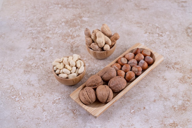 Una piccola tavola di legno piena di noci sane.