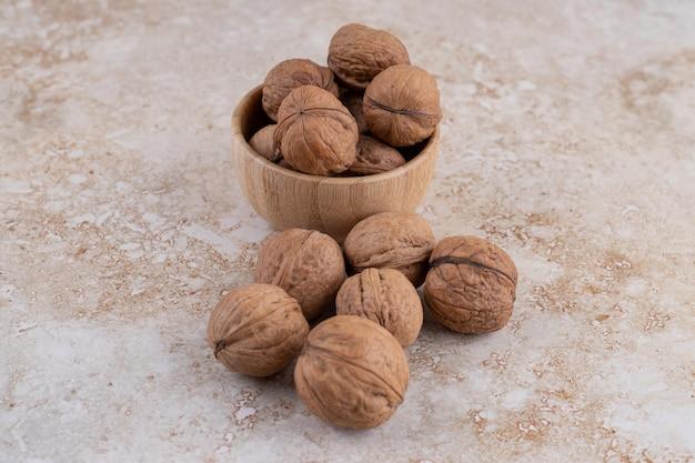 Una piccola ciotola di legno piena di noci sane. Foto Gratuite