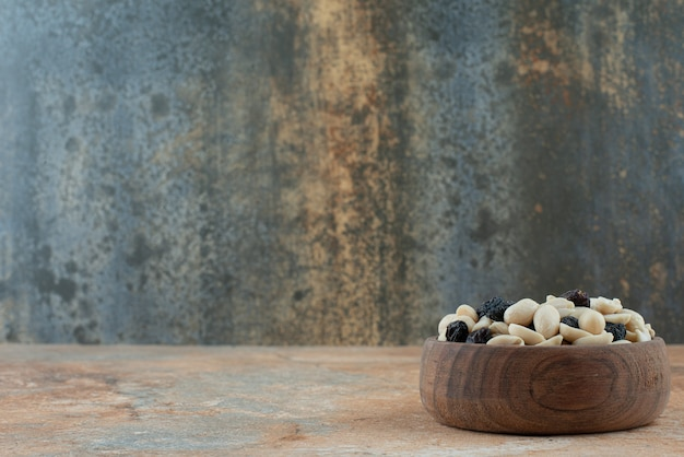 A small wooden bowl full of raisin and nuts on marble background